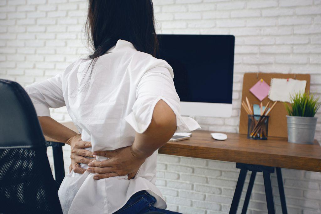 kobieta pracuje przed komputerem, niewygodne krzesło w biurze, bolące plecy