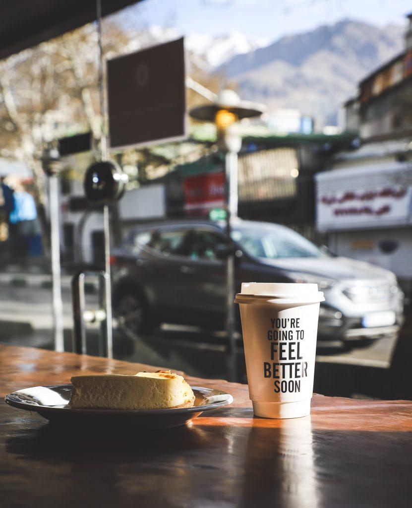 kubek kawy i kawałek ciasta w kawiarni z ładnym widokiem na góry