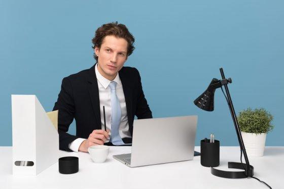 mężczyzna siedzący przy biurku z laptopem