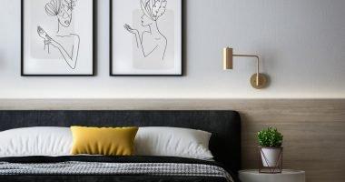 łóżko z poduszkami, szafka nocna obok łóżka, nad łóżkiem lampka kinkiet i plakaty