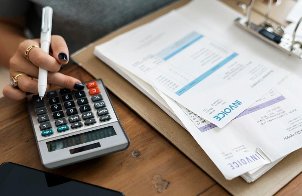 kobieta liczy na kalkulatorze faktury