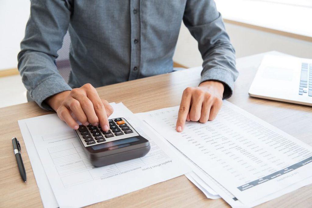 mężczyzna liczący na kalkulatorze i sprawdzający faktury