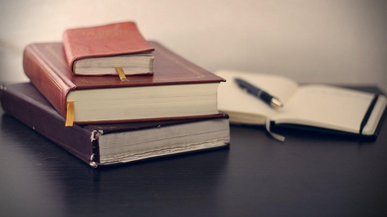 Książki, kalendarz i pióro leżą na biurku, stole